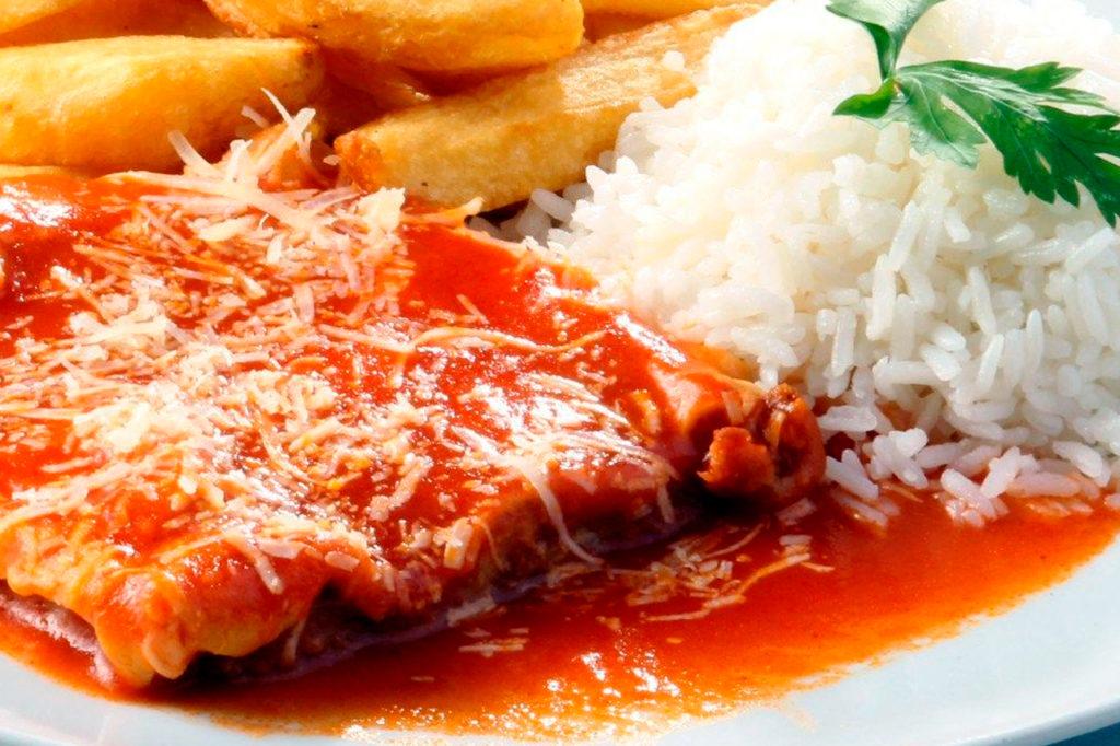 A imagem apresenta um Filé Mignon à Parmegiana com arroz e batatas.