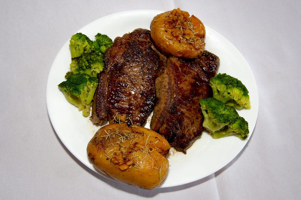 A imagem apresenta um prato branco com bife de chorizo, brócolis e batata.