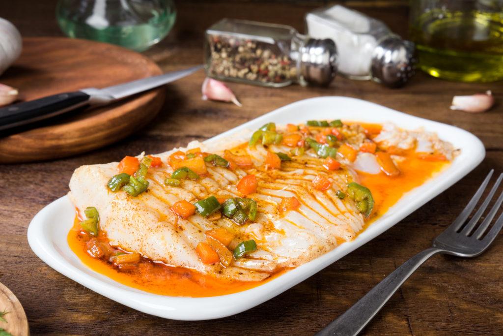 A imagem apresenta um prato branco em cima de uma mesa de madeira, com bacalhau cozido e pequenos pedaços de legumes por cima.